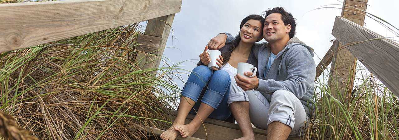 Young couple sitting on a beach drinking coffee