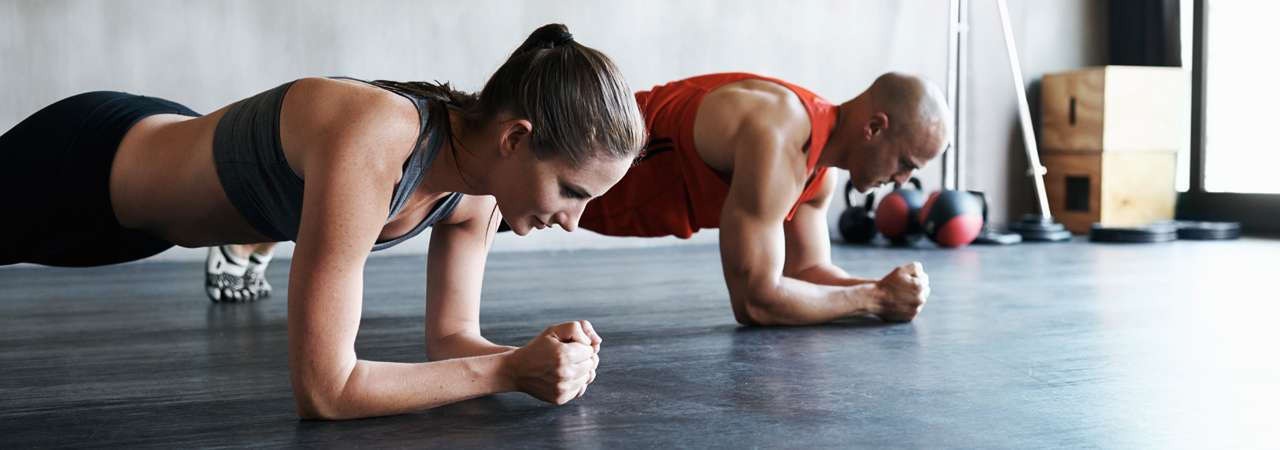 Image of man and woman doing push ups.