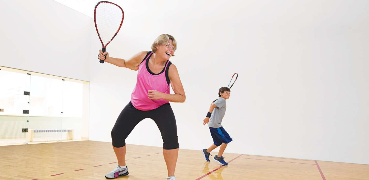 Mother and son playing racquet ball.