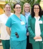Photo of four nurses standing in an atrium.