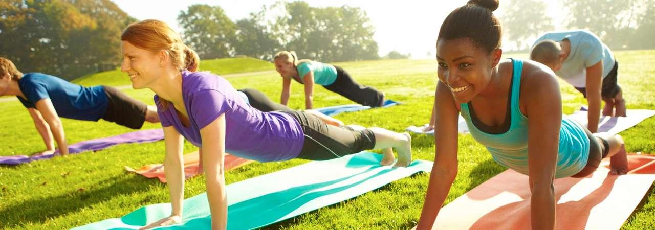 Image of women practicing yoga in park.