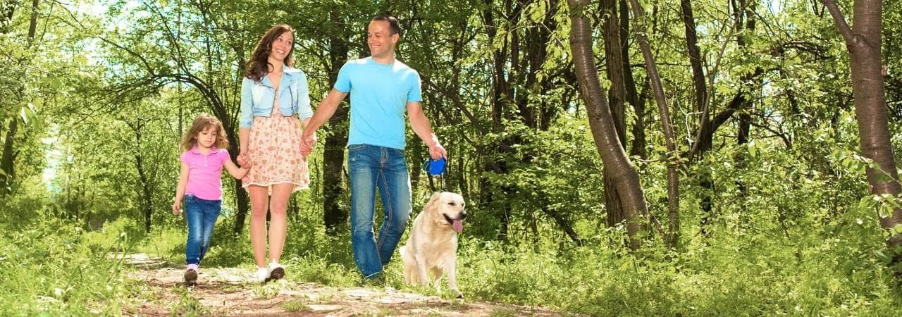 Image of family walking with their dog.
