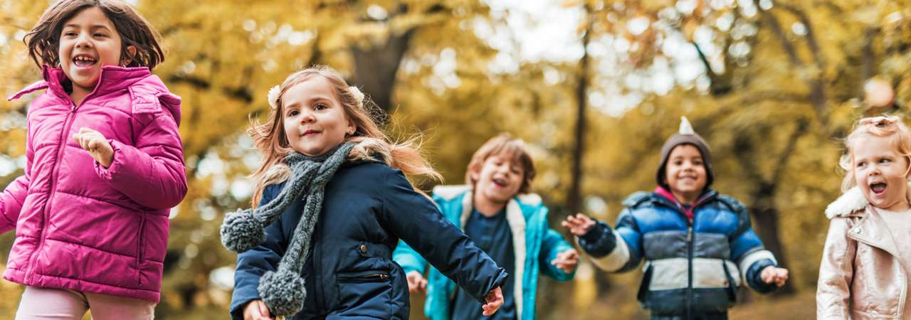 Photo of kids running outside on autumn day.