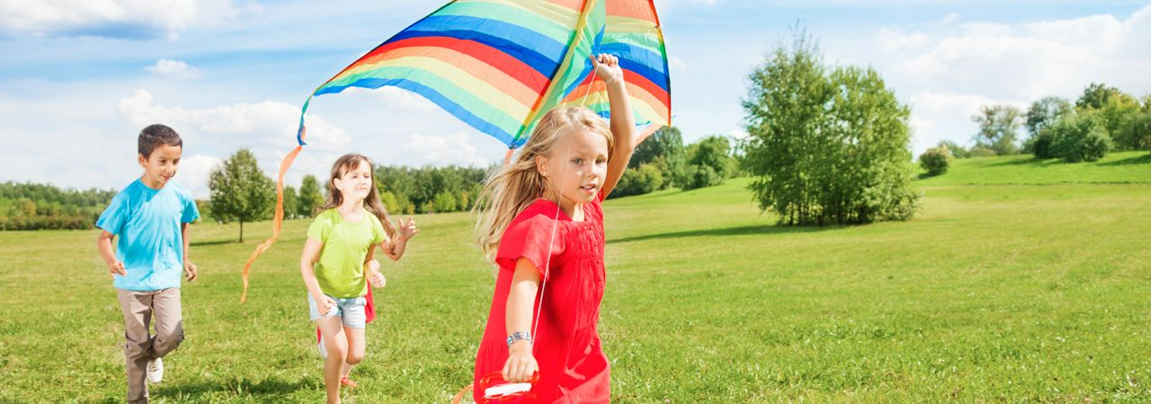 Image of three children with a kite.