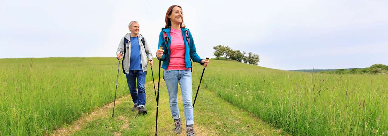 Image of mature couple Nordic walking.