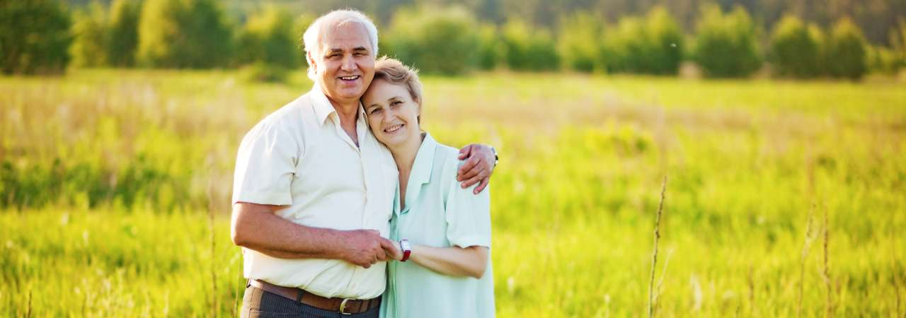 image of senior couple standing in field