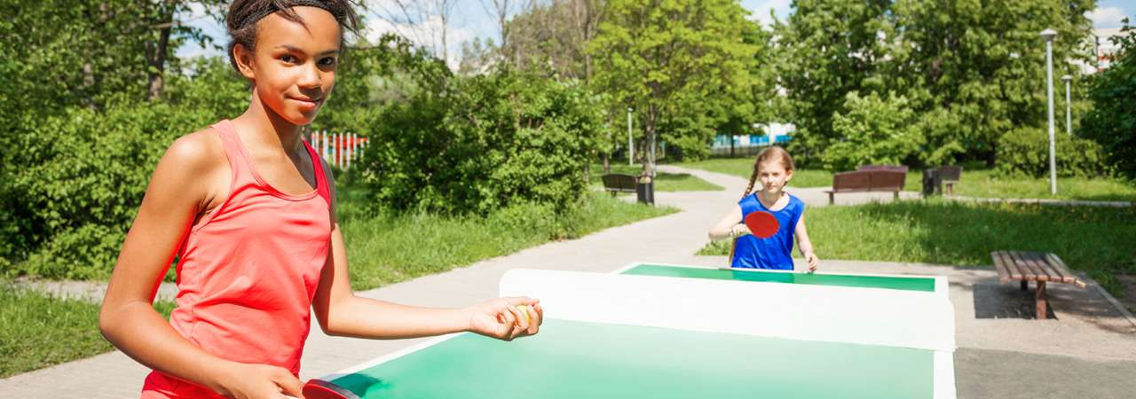 image of two girls playing ping pong outside