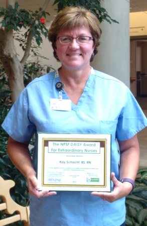 Nurse, Kay Schacht, holds award
