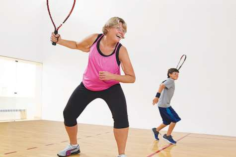 Photo of Cheryl playing racquetball with her son.