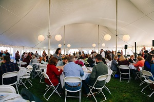 People sitting at tables under tent