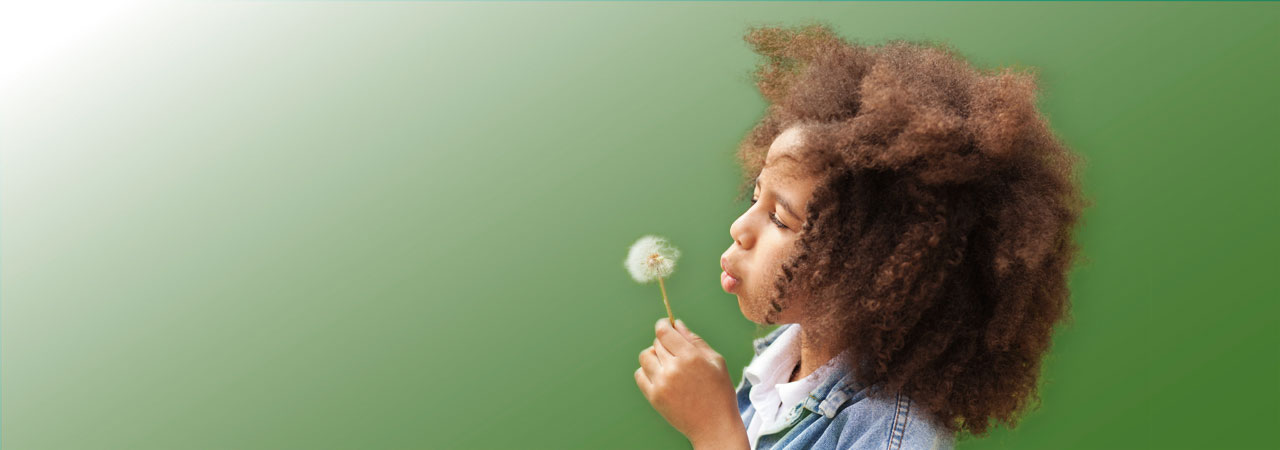 Photo of little girl blowing dandelion.