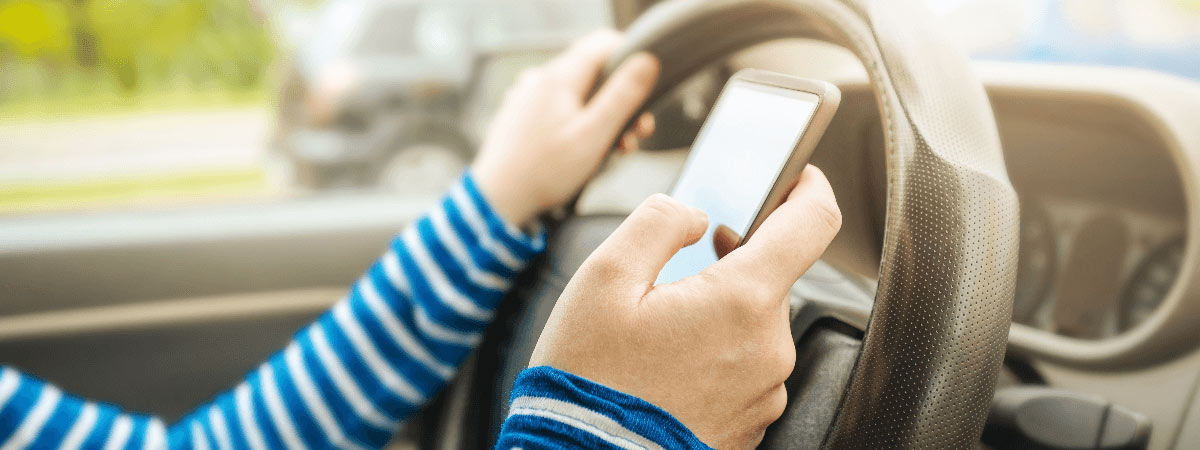 Image of person texting and driving.
