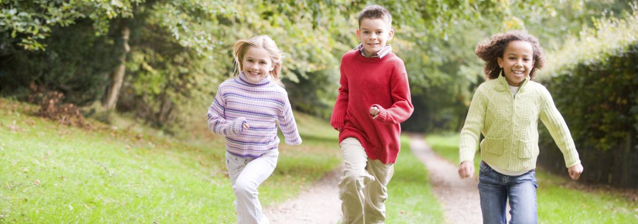 Photo of three children running down path.
