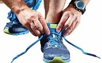 Image of a man lacing up his gym shoes