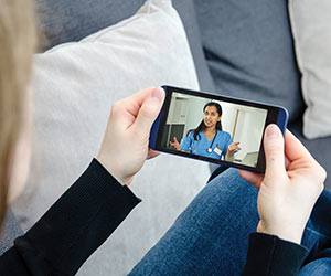 Photo of woman using her phone to speak with a doctor.