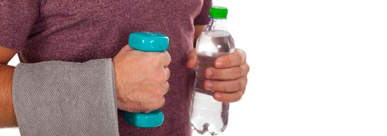 Photo of a man entering the group exercise studio with hand weights and a water bottle