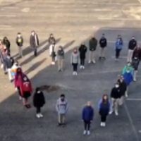 Photo of people standing in the shape of a heart.